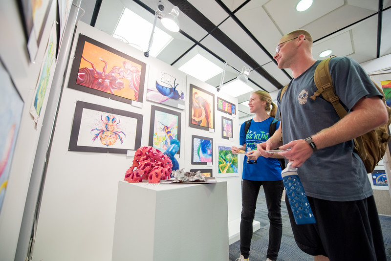 Kaitlyn Kronk (left) and Garrett Brundage stop by the Mary and Jeff Bell Library to look at the CCISD Art Gallery.