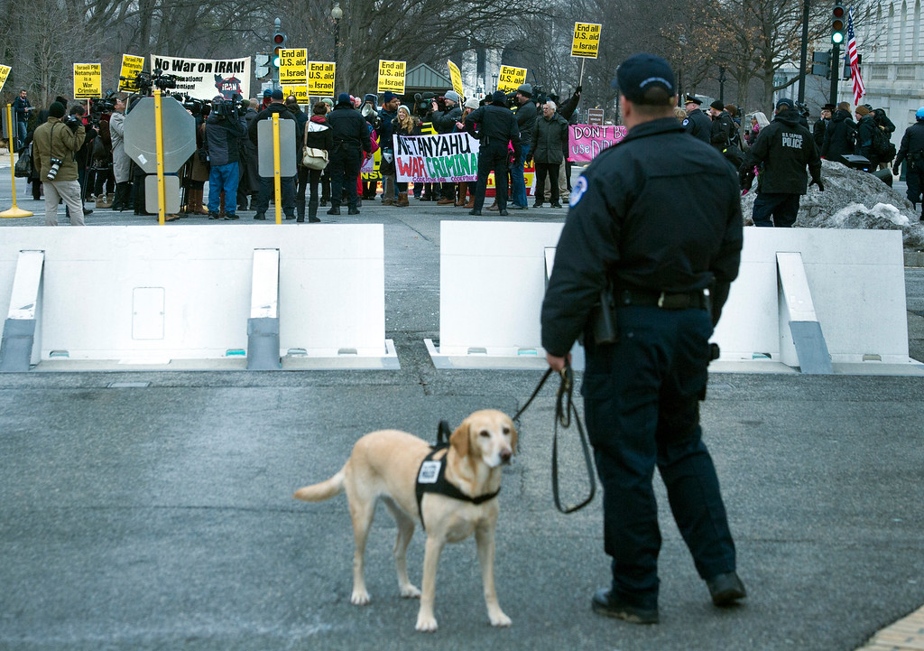 ". A Capitol Hill police officer watches as an anti-Israel protesters march on Capitol Hill in Washington, Tuesday, March 3, 2015, before Israeli Prime Minister Benjamin Netanyahu\'s address to a joint meeting of Congress. In a speech that stirred political intrigue in two countries, Netanyahu told Congress that negotiations underway between Iran and the U.S. would ""all but guarantee\"" that Tehran will get nuclear weapons, a step that the world must avoid at all costs. (AP Photo/Cliff Owen)"