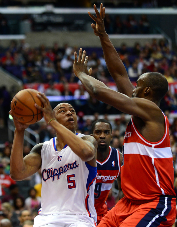 . Caron Butler of the Los Angeles Clippers (#5) looks to shoot under pressure from Emeka Okafor (R) and Martell Webster (C) of the Washington Wizards during their NBA game in Los Angeles on January 19, 2013.  FREDERIC J. BROWN/AFP/Getty Images