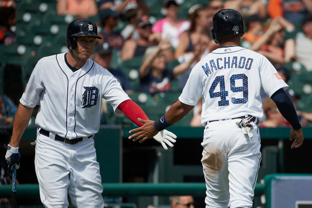 . Detroit Tigers Dixon Machado (49) receives congratulations from Matt den Dekker after scoring against the Cleveland Indians in the seventh inning of a baseball game in Detroit, Sunday, July 2, 2017. (AP Photo/Rick Osentoski)