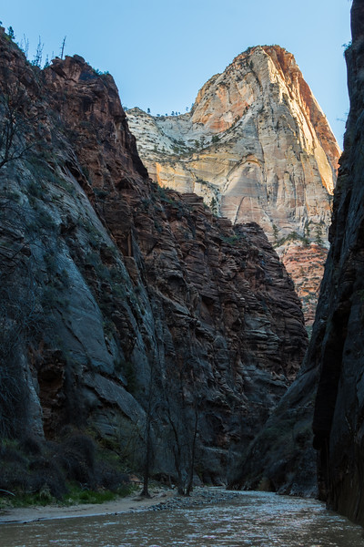 Mountains are seen splashed with morning sun high above the Virgin River from deep inside Zion Canyon in Zion National Park