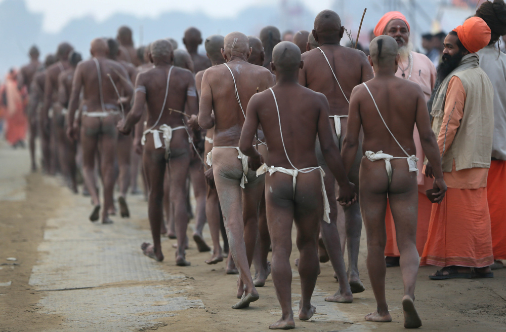 """. Hindu holy men of the Juna Akhara sect walk after rituals that are believed to rid them of all ties in this life and dedicate themselves to serving God as a \""""Naga\"""" or naked holy men, at Sangam, the confluence of the Ganges and Yamuna River during the Maha Kumbh festival in Allahabad, India, Wednesday, Feb. 6, 2013. The significance of nakedness is that they will not have any worldly ties to material belongings, even something as simple as clothes. This ritual that transforms selected holy men to Naga can only be done at the Kumbh festival.(AP Photo /Manish Swarup)"""
