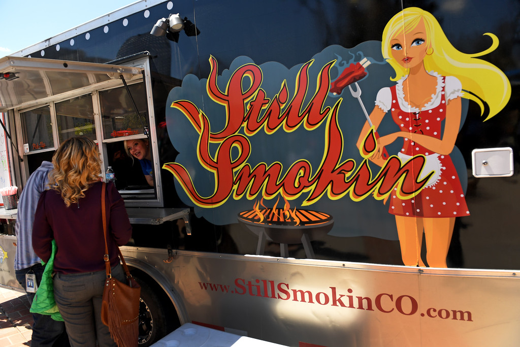 . Robyn Gray, left, serves people  delicious southern inspired fusion BBQ  food from Still Smokin\' Food truck at Civic Center Park on the first day of the 11th annual Civic Center EATS on May 3, 2016 in Denver, Colorado. (Photo by Helen H. Richardson/The Denver Post)
