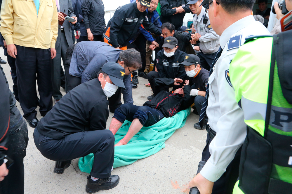 . A rescued passenger from a ferry sinking off South Korea\'s southern coast, is carried by police and rescue teams on his arrival at Jindo port in Jindo, south of Seoul, South Korea, Wednesday, April 16, 2014. Dozens of rescue boats and helicopters are scrambling to save more than 470 people, including many high school students, caught on a ferry sinking off South Korea\'s southern coast, officials said. There are no immediate reports of causalities. (AP Photo/Park Chul-heung, Yonhap)