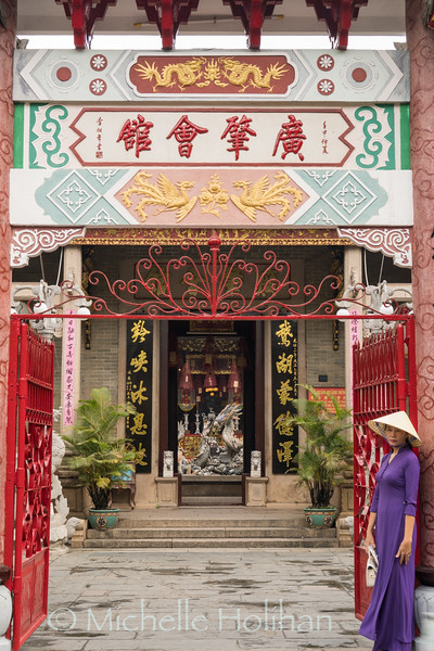 HOI AN, VIETNAM - MARCH 6, 2019: Unidentified woman poses for a picture in front of a temple.