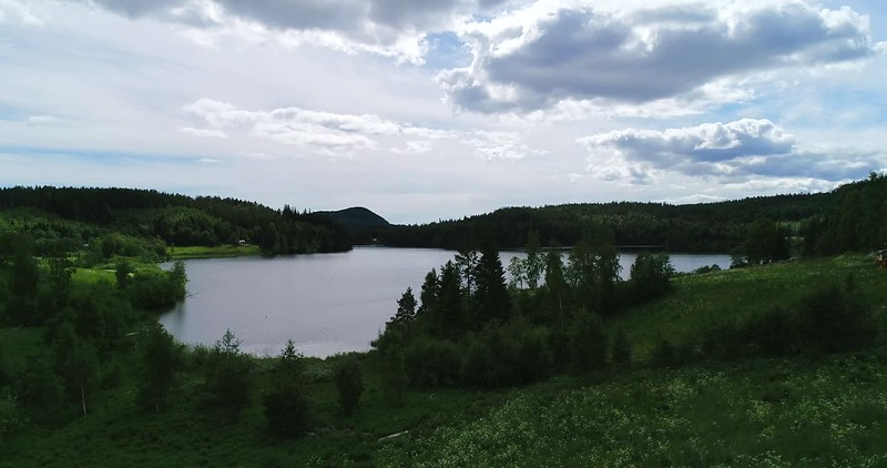 Aerial: flying towards a lake surrounded by wooded hills