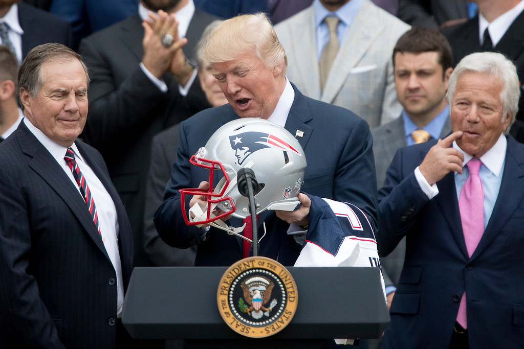 . President Donald Trump. flanked by New England Patriots head coach Bill Belichick, left, and owner Robert Kraft, holds a New England Patriots football helmet and jersey during a ceremony on the South Lawn of the White House in Washington, Wednesday, April 19, 2017, where he honored the Super Bowl Champion New England Patriots for their Super Bowl LI victory. (AP Photo/Andrew Harnik)