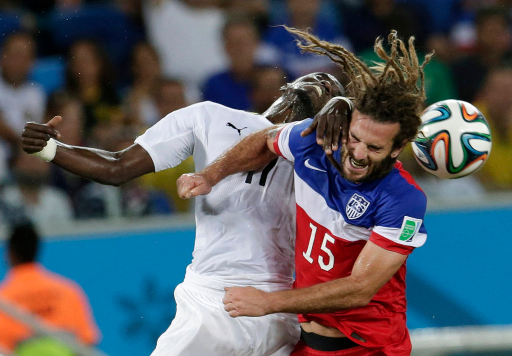 Description of . Ghana's Mohammed Rabiu, left, and United States' Kyle Beckerman struggle with each other to head the ball during the group G World Cup soccer match between Ghana and the United States at the Arena das Dunas in Natal, Brazil, Monday, June 16, 2014.  (AP Photo/Petr David Josek)