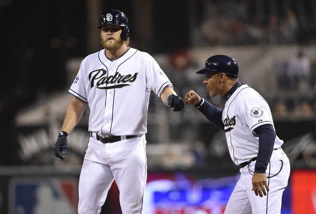 . SAN DIEGO, CA - APRIL 16:  Andrew Cashner #34 of the San Diego Padres is congratulated by Jose Valentin #17 after hitting a single during the third inning of a  baseball game against the Colorado Rockies at Petco Park April 16, 2014 in San Diego, California.  (Photo by Denis Poroy/Getty Images)