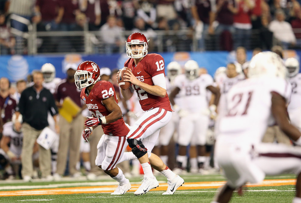Description of . Landry Jones #12 of the Oklahoma Sooners passes against the Oklahoma Sooners during the Cotton Bowl at Cowboys Stadium on January 4, 2013 in Arlington, Texas.  (Photo by Ronald Martinez/Getty Images)