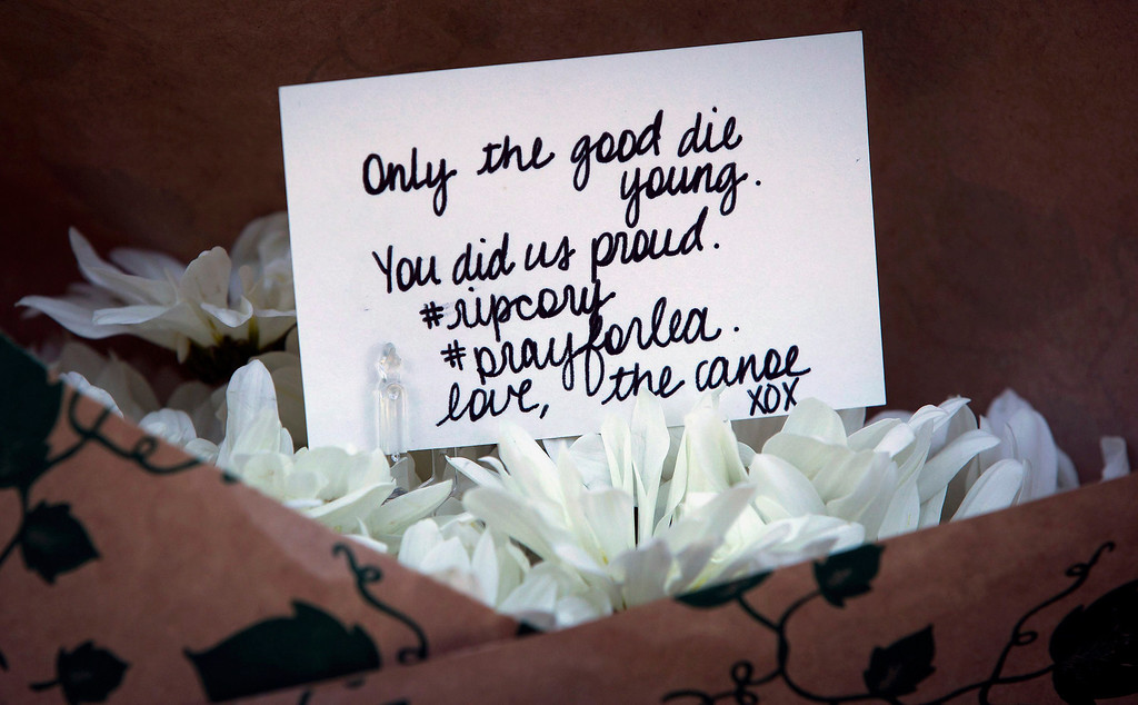 . A handwritten card is placed among flowers at a small memorial to Canadian actor Cory Monteith outside the Fairmont Pacific Rim Hotel in Vancouver, British Columbia, on Sunday July 14, 2013. Monteith\'s body was found in a room at the hotel Saturday. (AP Photo/The Canadian Press, Darryl Dyck)