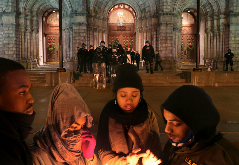 . St. Louis Police officers guard the entrance to the Cathedral Basilica before Midnight Mass as protesters held a candlelight vigil on Wednesday, Dec. 24, 2014, in St. Louis. The mayor of the St. Louis suburb of Berkeley urged calm Wednesday after a white police officer killed black 18-year-old Antonio Martin who police said pointed a gun at him, reigniting tensions that have lingered since the death of Michael Brown in neighboring Ferguson. (AP Photo/St. Louis Post-Dispatch, Robert Cohen)