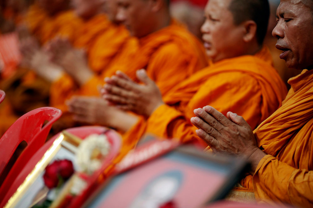 """. Buddhist monks join members of the \""""red shirt\"""" movement in prayer during a gathering near the Democracy Monument, the site of bloody clashes with Thai security forces, in Bangkok on April 10, 2013. Supporters of Thaksin Shinawatra, the former prime minister, and members of the \""""red shirt\"""" movement gathered in Bangkok on Wednesday to mark the third anniversary of bloody clashes and to commemorate their deceased comrades.   REUTERS/Damir Sagolj"""