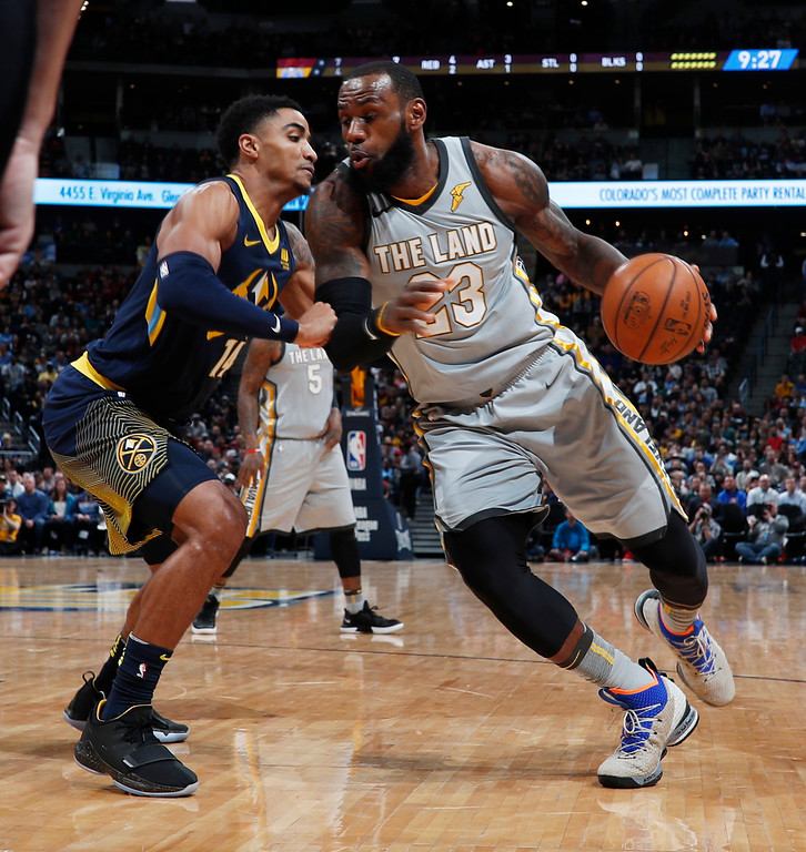 . Denver Nuggets guard Gary Harris, left, defends as Cleveland Cavaliers forward LeBron James drives to the basket during the first half of an NBA basketball game Wednesday, March 7, 2018, in Denver. (AP Photo/David Zalubowski)