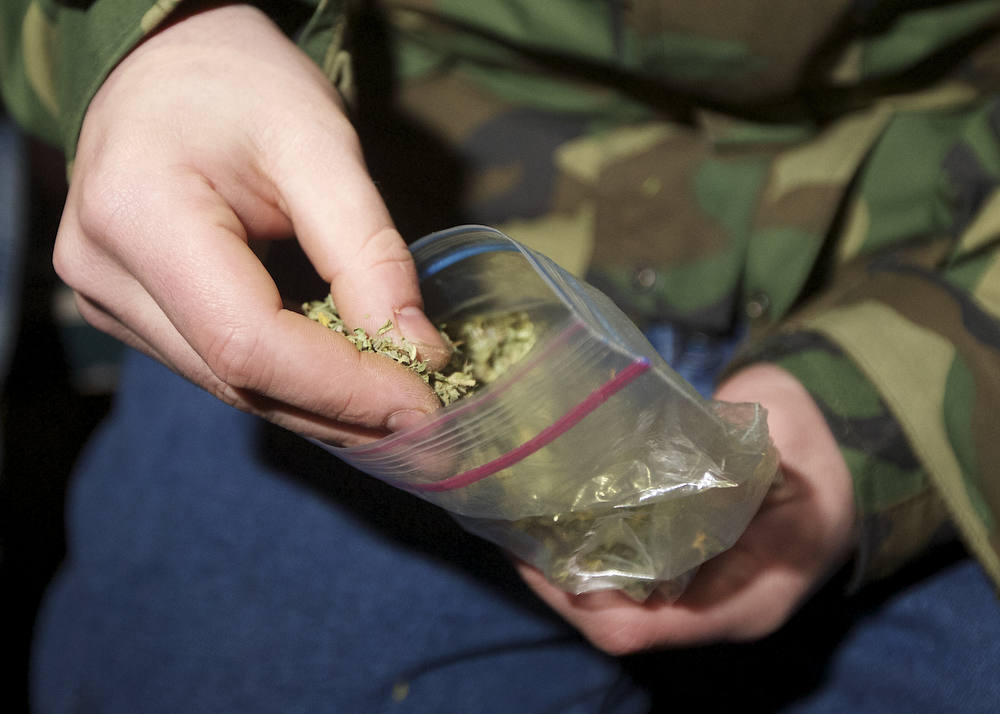 Description of . A Seattle resident takes marijuana from a plastic bag shortly after a law legalizing the recreational use of  marijuana took effect on December 6, 2012 in Seattle, Washington.  Voters approved an initiative to decriminalize the recreational use of marijuana making it one of the first states to do so. (Photo by Stephen Brashear/Getty Images)