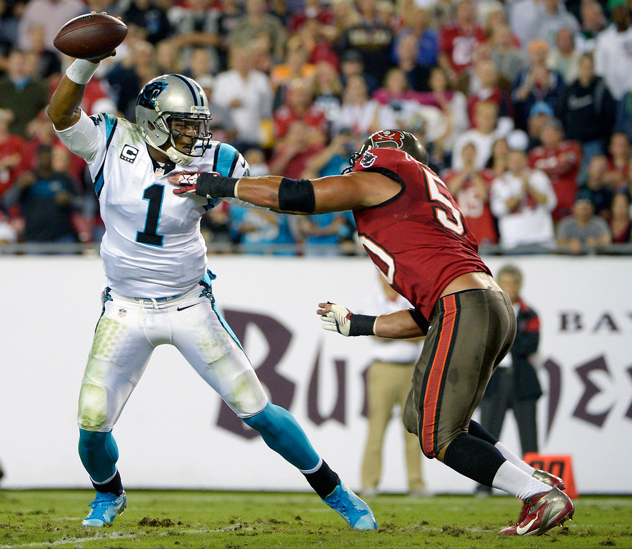 . Carolina Panthers quarterback Cam Newton (1) scrambles to get away from Tampa Bay Buccaneers defensive end Daniel Te\'o-Nesheim, right, during the first half of an NFL football game in Tampa, Fla., Thursday, Oct. 24, 2013. (AP Photo/Phelan M. Ebenhack)