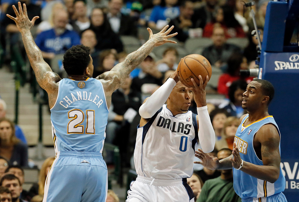 . Dallas Mavericks forward Shawn Marion (0) looks for an open teammate as Denver Nuggets\' Wilson Chandler (21) and Darrell Arthur (00) defend during the first half of an NBA basketball game Monday, Nov. 25, 2013, in Dallas. (AP Photo/Brandon Wade)