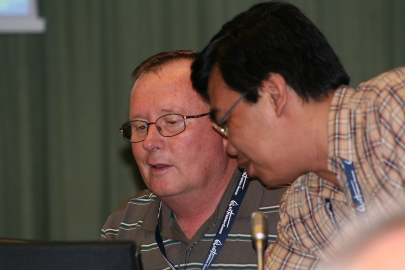 Fr. Leo Heck gets a bit of technical assistance from Fr. Madya