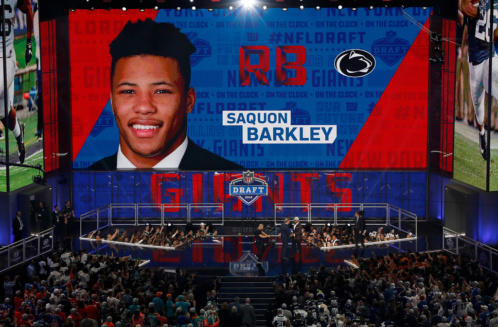 . Penn State\'s Saquon Barkley greets commissioner Roger Goodell on the stage after being selected by the New York Giants during the first round of the NFL football draft, Thursday, April 26, 2018, in Arlington, Texas. (AP Photo/David J. Phillip)
