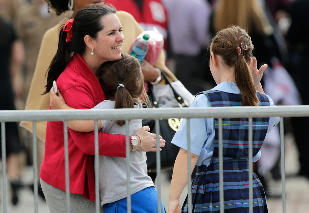 . A woman hugs her child while reuniting at a gathering point for family members of Navy Yard employees that was set up inside Nationals Park in the wake of the shooting September 16, 2013 in Washington, DC. Police believe at least one gunman shot and killed at least 12 people and wounded others in an incident that put parts of the city on lockdown. (Photo by Win McNamee/Getty Images)