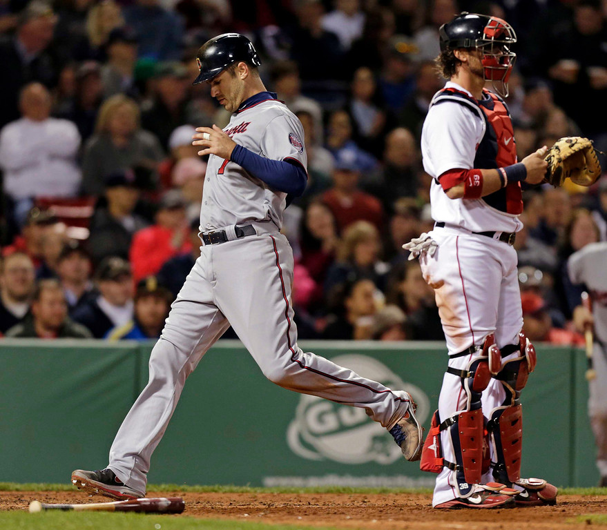 . Minnesota Twins\' Joe Mauer passes Boston Red Sox catcher Jarrod Saltalamacchia, right, as he crosses the plate after being driven in on a sacrifice fly by Justin Morneau during the fifth inning. (AP Photo/Charles Krupa)
