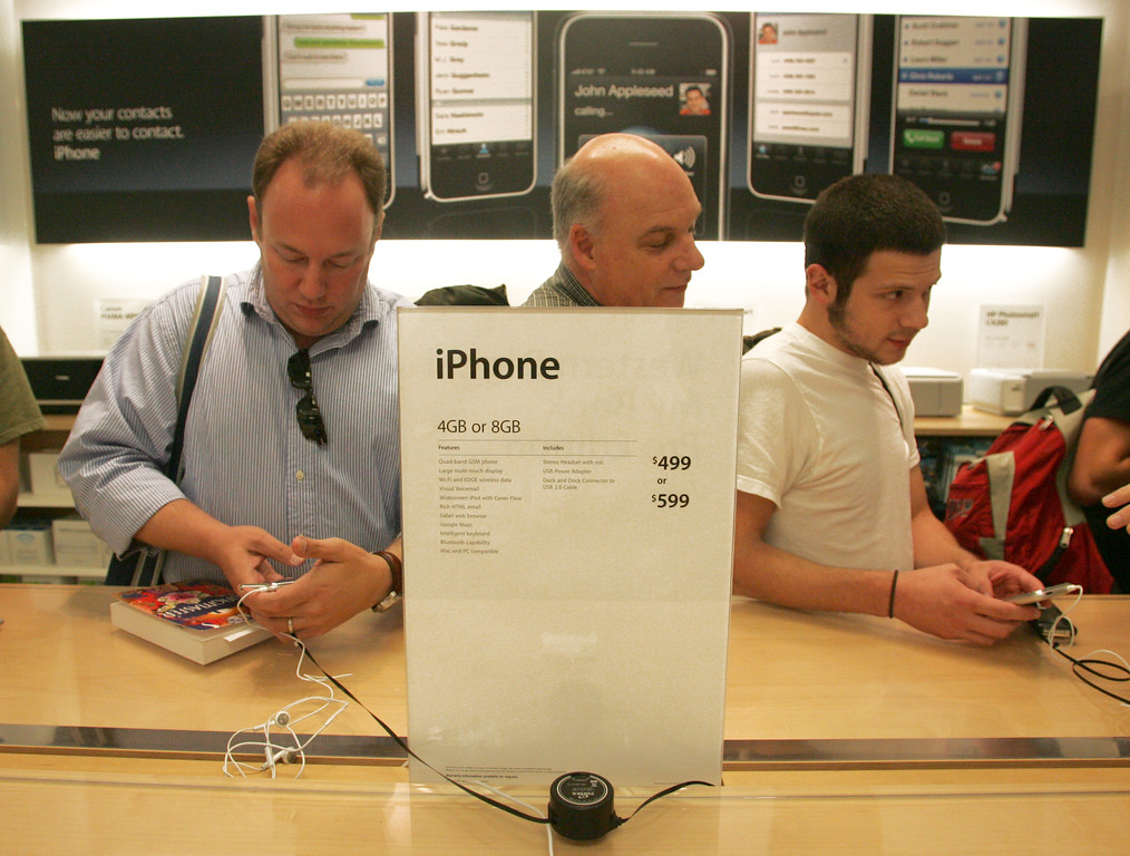 . Customers examine the functions on the new iPhone on the first day of sales for the device, Friday, June 29, 2007, at an Apple store at Southpark Mall in Charlotte, N.C. (AP Photo/Jason E. Miczek).