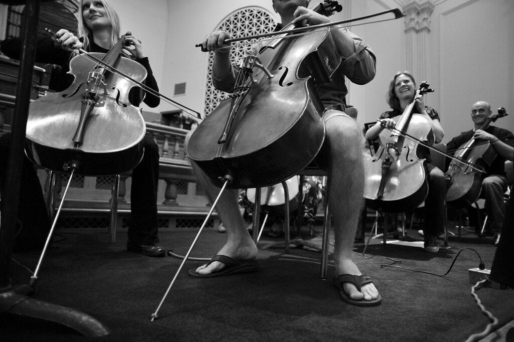""". Principal cellist Bryan Scafuri leads his section wearing shorts and sandals during a rehearsal with the Denver Philharmonic Orchestra at the KPOF Concert Hall in Denver, CO, Monday September 24, 2012.  Scafuri said the cello was a simple choice, \""""That belongs to my mother. She was a public school orchestra teacher for 34 years. She played the cello as well. So I grew up listening to the cello at home. When it came time to chose, it was pretty obvious. I always wanted to play the cello. I didn\'t like the squeaky sound of the violin, I like the more mellow sound of the cellos.\"""" Scafuri, 28, said he started in 4th grade and never stopped playing, he received his Masters in cello performance from Miami University of Ohio in 2009.   \""""I play with 2 other orchestras so I travel a lot. I also teach cello privately on the side.\"""" Craig F. Walker, The Denver Post"""
