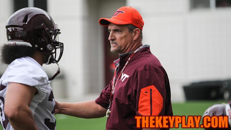 Defensive coordinator Bud Foster talks with LB Dahman McKinnon during position drills. (Mark Umansky/TheKeyPlay.com)