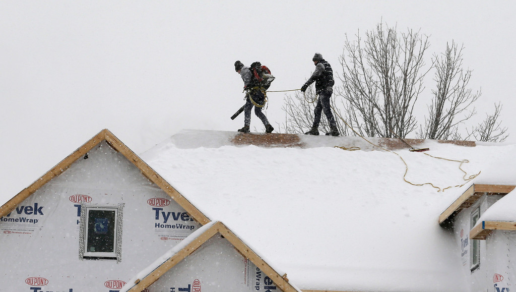 . Two men clear snow from a roof of a new home with a leaf blower, Wednesday, Feb. 5, 2014, in Pepper Pike, Ohio. Most of Ohio was hit with another bout of heavy snow and freezing rain, closing hundreds of schools and creating extremely hazardous driving conditions. Much of the state was slammed with 4 to 8 inches of snow overnight.  (AP Photo/Tony Dejak)