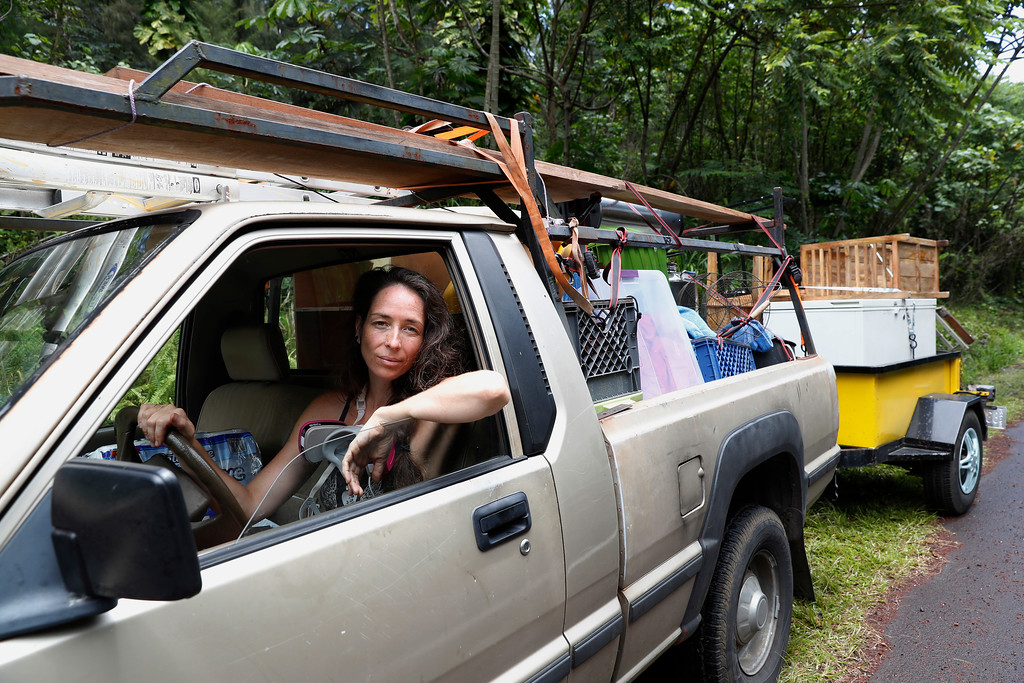 . Laura Dawn is seen in her truck loaded with her possessions as she and her husband flee the lava eruption, Sunday, May 6, 2018, near Pahoa, HI. Their property is just below the active lava eruption and they fear their land will get covered in lava. They are moving further upcoast to a safer area. (AP Photo/Marco Garcia)