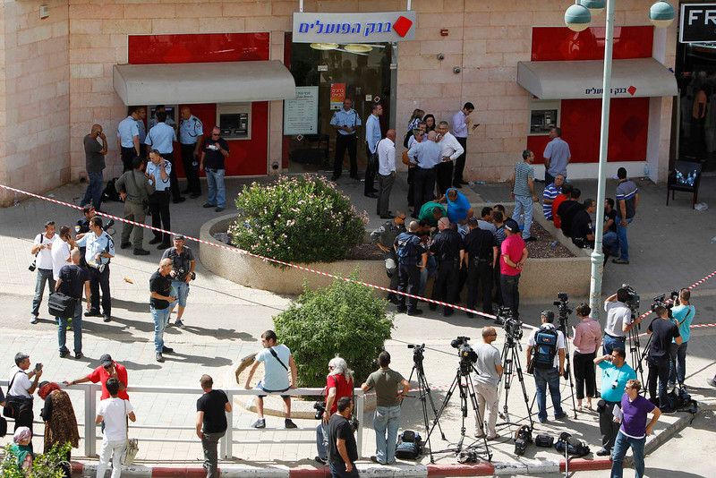. Members of the media and police special forces stand outside a Bank Hapoalim branch after a shooting at the bank in the southern city of Beersheba May 20, 2013. A gunman shot dead four people execution-style in the bank in Israel on Monday after being refused an overdraft and cash from its automatic teller machine. The assailant, identified by media reports as a former paramilitary border policeman, killed himself after police raided the branch to free his hostages. REUTERS/Amir Cohen