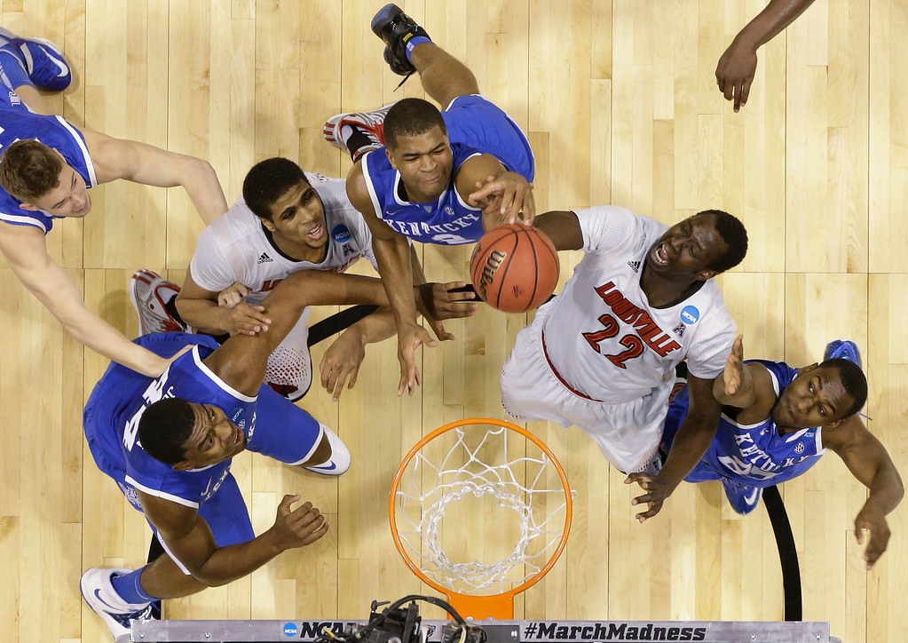 . Kentucky\'s Dakari Johnson (44), Aaron Harrison (2) and Dominique Hawkins (25) go after a rebound with Louisville\'s Wayne Blackshear (20) and Akoy Agau (22) during the first half of an NCAA Midwest Regional semifinal college basketball tournament game Friday, March 28, 2014, in Indianapolis. (AP Photo/Michael Conroy)