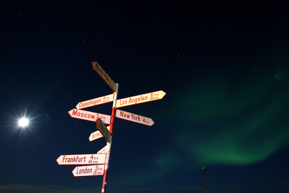 . The Aurora Borealis glows over a direction sign naming famous capital cities of the world in the Kangerlussuaq Airport September 3, 2007, near the Greenland town of Kangerlussuaq. Greenlanders voted on November 25, 2008 on its relationship to Denmark with 76 percent of voters favoring looser political ties. The Northern Lights most often occurs from September to October and from March to April and are a popular tourist attraction.  (Photo by Uriel Sinai/Getty Images)