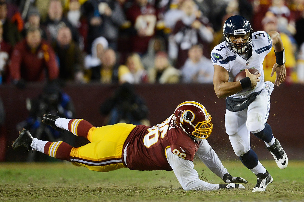 . Russell Wilson #3 of the Seattle Seahawks runs the ball for a first down in the third quarter against the defense of  Barry Cofield #96 of the Washington Redskins during the NFC Wild Card Playoff Game at FedExField on January 6, 2013 in Landover, Maryland.  (Photo by Patrick McDermott/Getty Images)