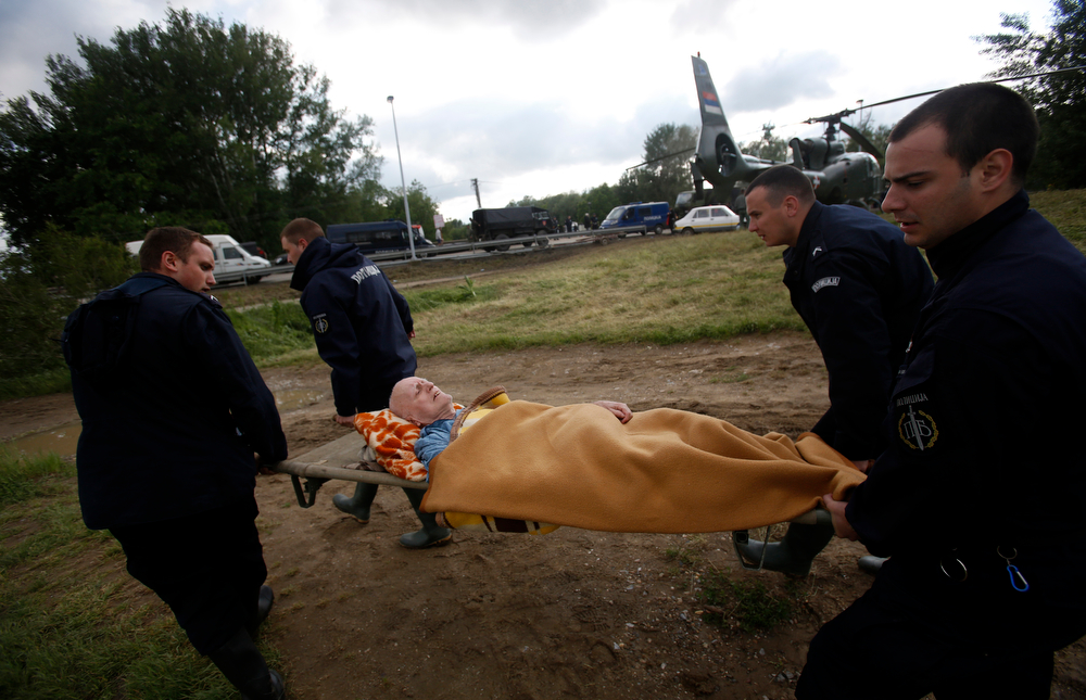 Description of . Serbian police officers carry a man from a military helicopter during flood evacuation from Obrenovac, some 30 kilometers (18 miles) southwest of Belgrade Serbia, Saturday, May 17, 2014. Record flooding in the Balkans leaves at least 20 people dead in Serbia and Bosnia and is forcing tens of thousands to flee their homes. Meteorologists say the flooding is the worst since records began 120 years ago. (AP Photo/Darko Vojinovic)