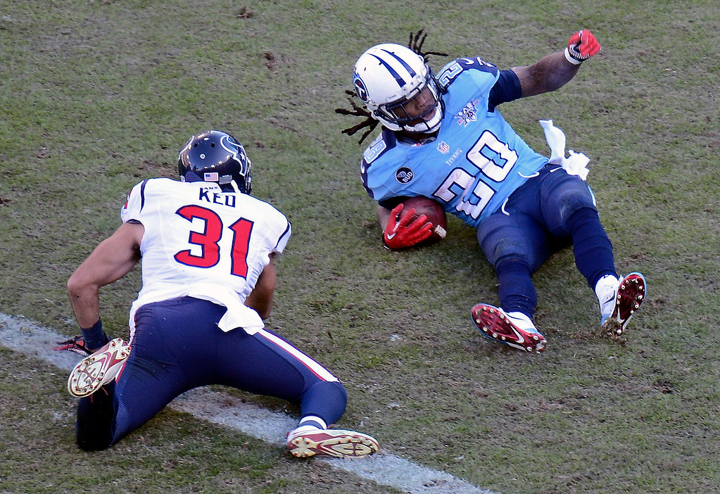 . Tennessee Titans running back Chris Johnson (28) falls into the end zone to score a touchdown on an 11-yard run as he is defended by Houston Texans free safety Shiloh Keo (31) in the third quarter of an NFL football game on Sunday, Dec. 29, 2013, in Nashville, Tenn. (AP Photo/Mark Zaleski)