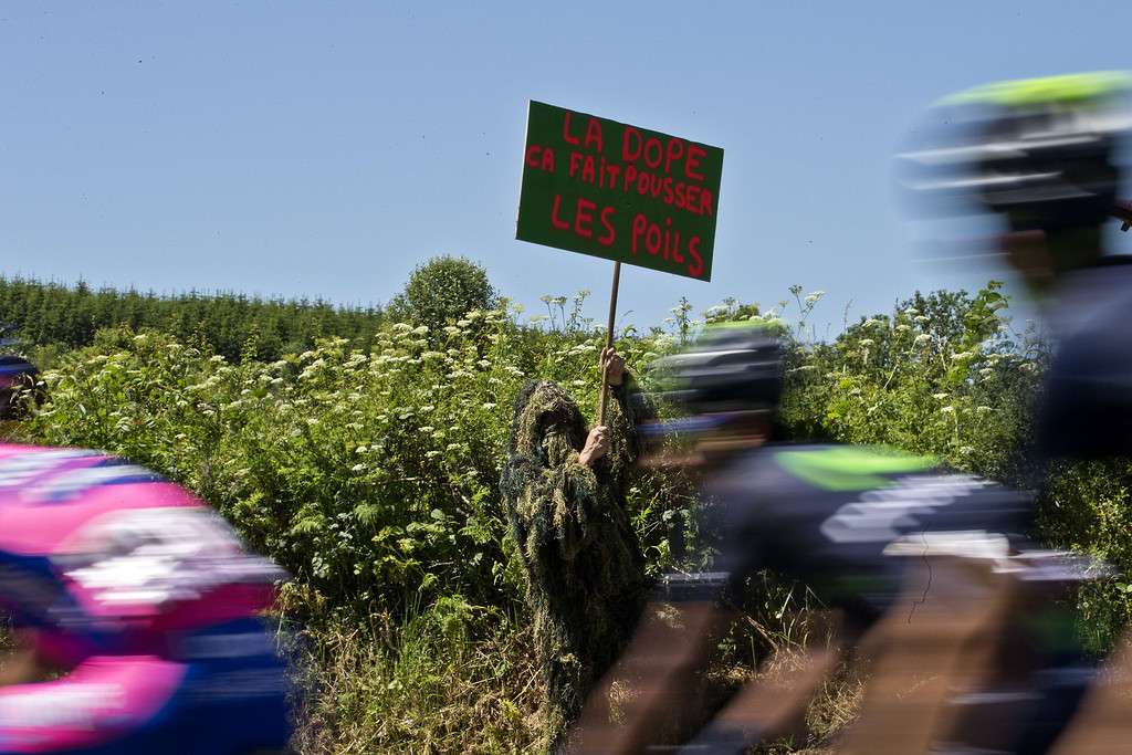 """. Cyclists ride past a man holding a placard reading \""""Dope makes hair grow\"""" during the 205.5 km seventh stage of the 100th edition of the Tour de France cycling race on July 5, 2013 between Montpellier and Albi, southwestern France.  JOEL SAGET/AFP/Getty Images"""
