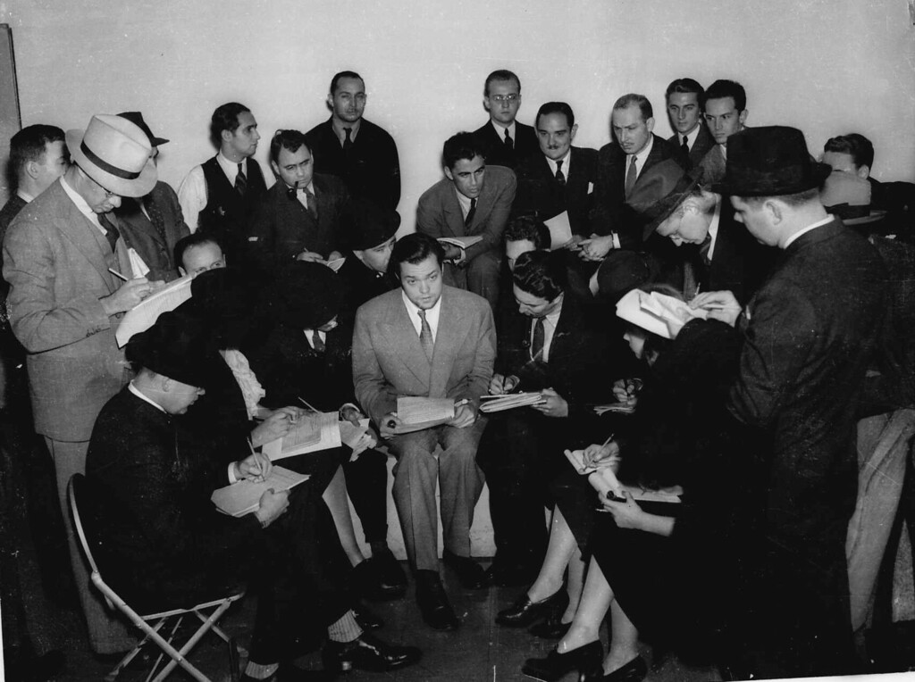 """. Orson Welles, center, young director who presented the dramatization of H.G. Wells\' \""""War of the Worlds\"""" on Sunday night, Oct. 30, 1938 speaks with the press the next day.  The radio broadcast caused great panic among radio listeners amazed that his dramatization had been so realistic.   (AP Photo)"""