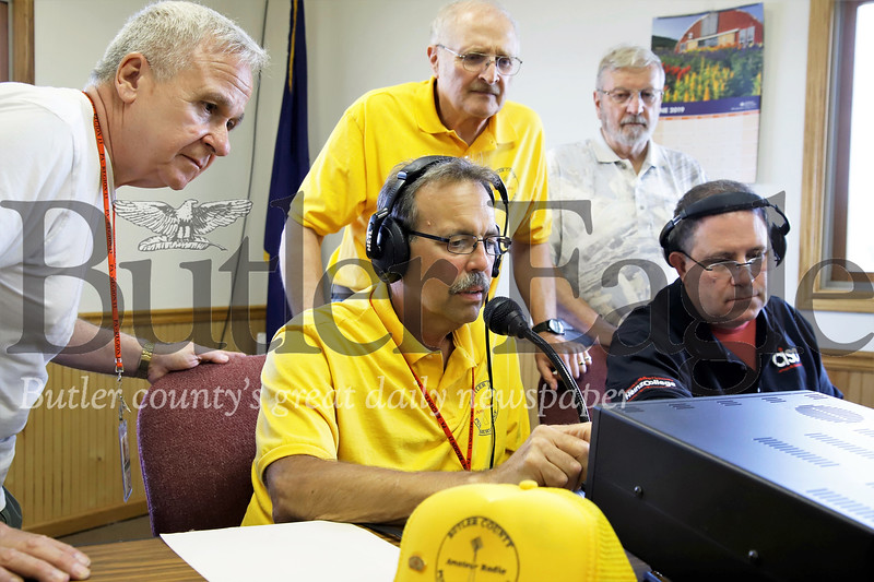 Julian Savage (left) Dan Metrick and Tom McCracken look on as Denny Stokes (front/center)  and Tom Grasso adjust signals on one of four radio operation stations in the Winfield Township building. Seb Foltz/Butler Eagle