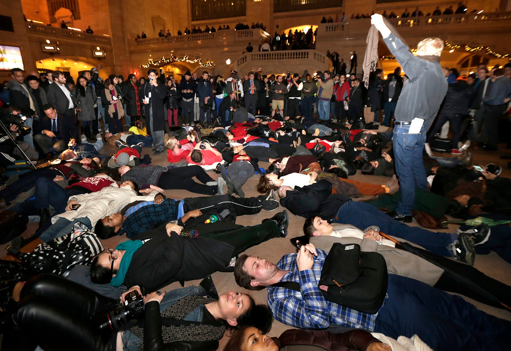 . People lie on the ground at Grand Central Terminal after it was announced that the New York City police officer involved in the death of Eric Garner is not being indicted, Wednesday, Dec. 3, 2014, in New York. A grand jury cleared the white New York City police officer Wednesday in the videotaped chokehold death of Garner, an unarmed black man, who had been stopped on suspicion of selling loose, untaxed cigarettes, a lawyer for the victim\'s family said. A video shot by an onlooker and widely viewed on the Internet showed the 43-year-old Garner telling a group of police officers to leave him alone as they tried to arrest him. The city medical examiner ruled Garner\'s death a homicide and found that a chokehold contributed to it. (AP Photo/Julio Cortez)