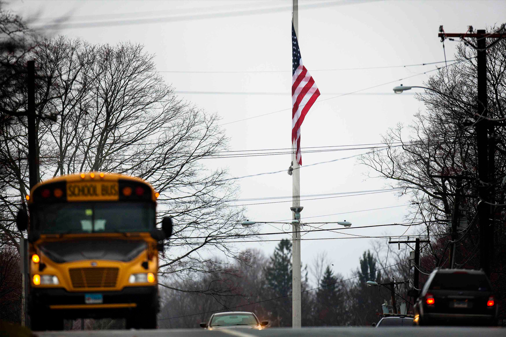 Description of . A school bus stands parked on the side of a road beside a flag lowered to half mast in honor of the victims of the recent shooting in Sandy Hook Village in Newtown, Connecticut December 18, 2012. The schools of Newtown, which stood empty in the wake of a shooting rampage that took 26 of their own, will again ring with the sounds of students and teachers on Tuesday as the bucolic Connecticut town struggles to return to normal. REUTERS/Lucas Jackson