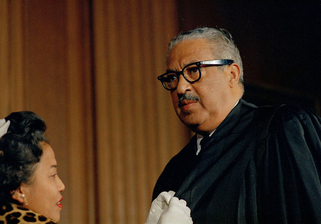 . Thurgood Marshall, first black Associate Justice of the Supreme Court, is photographed on his first day in court wearing judicial robes, Oct. 2, 1967. Helping him with buttons is his wife Cecilia Suyat. (AP Photo/Bob Schutz)
