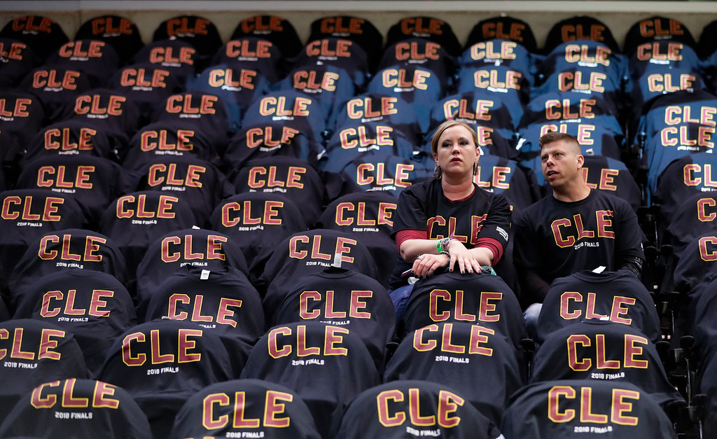 . Fans wait while surrounded by T-shirt-covered seats before Game 3 of basketball\'s NBA Finals between the Cleveland Cavaliers and the Golden State Warriors, Wednesday, June 6, 2018 in Cleveland. (AP Photo/Tony Dejak)