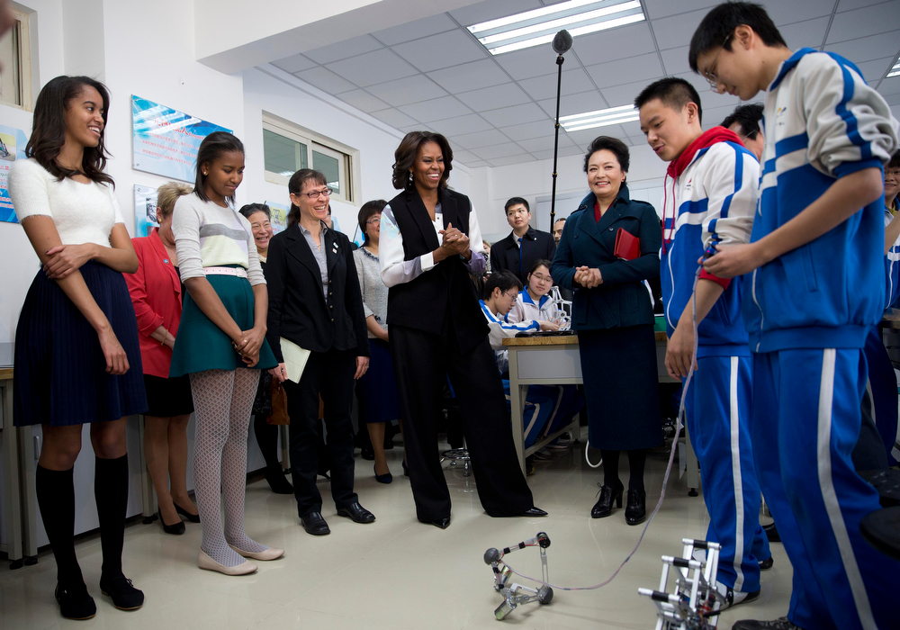 . U.S. First Lady Michelle Obama, center, her daughters Malia, left, and Sasha, second from left, is accompanied by Peng Liyuan, wife of Chinese President Xi Jinping, third from right, watch students demonstrating remote control mechanical robots at the Beijing Normal School, a school that prepares students to attend universities abroad in Beijing, China Friday, March 21, 2014. (AP Photo/Andy Wong, Pool)