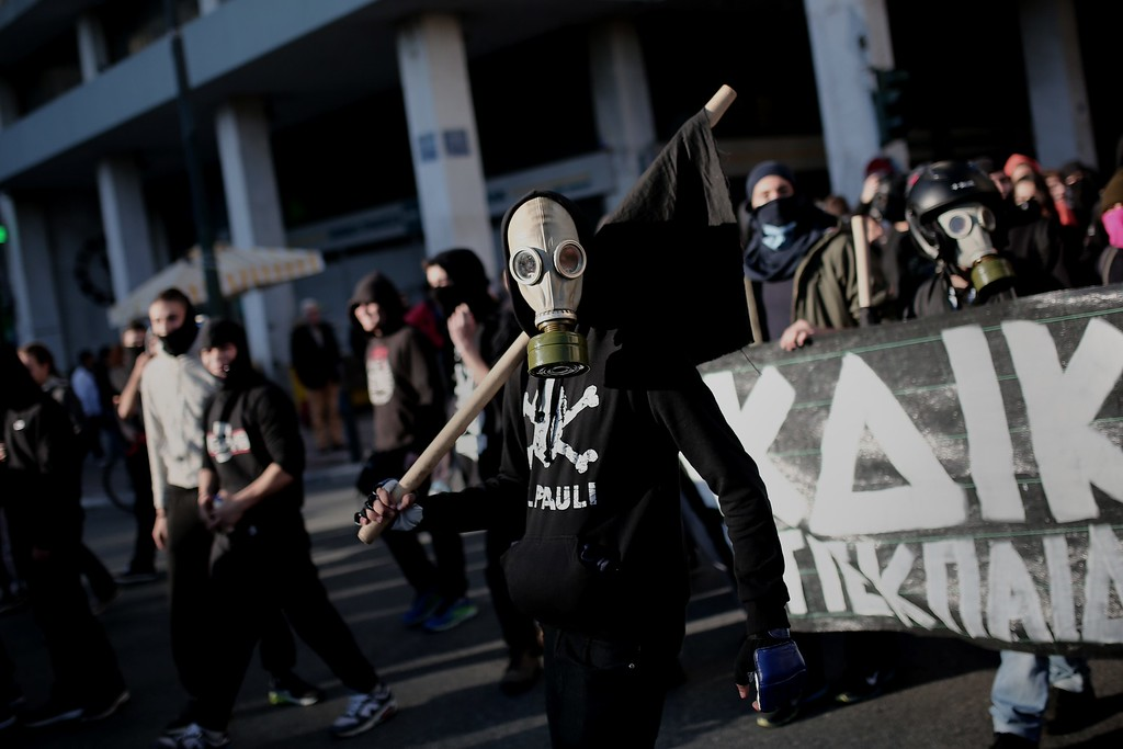 . A protester wearing a gas mask holds a black flags as he takes part in a protest march in Athens on December 6, 2014, to commemorate the six-year anniversary of the fatal shooting of teenager Alexis Grigoropoulos by a police officer, an event that plunged Greece into weeks of youth riots.  AFP PHOTO / ANGELOS TZORTZINIS/AFP/Getty Images