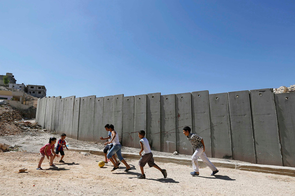 . Palestinian children play near a section of the controversial Israeli barrier in Shuafat refugee camp in the West Bank near Jerusalem July 29, 2013. Israeli and Palestinian officials put forward clashing formats for peace talks due to resume in Washington on Monday for the first time in nearly three years after intense U.S. mediation. It is unclear how the United States hopes to bridge the core issues in the dispute, including borders, the future of Jewish settlements on the West Bank, the fate of Palestinian refugees and the status of Jerusalem.       REUTERS/Ammar Awad