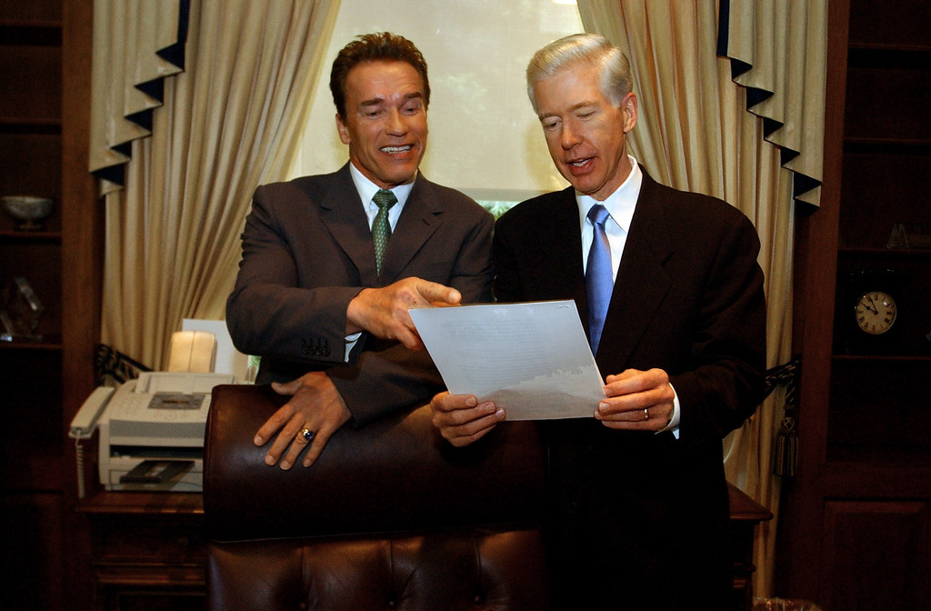 . Gov. Gray Davis, right, goes over one of the transition papers prepared for Gov.-elect Arnold Schwarzenegger, left, in the governor\'s private office at the Capitol in Sacramento, Calif., Thursday, Oct. 23, 2003.  The two met for the first time since the election to go discuss the transition.(AP Photo/Rich Pedroncelli)