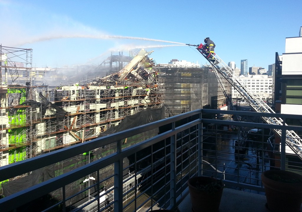 . Firefighters continue to pour water on hotspots the day after a five-alarm fire destroyed an apartment complex in San Francisco\'s Mission Bay area on Wednesday, March 12, 2014.   (Courtesy of Chris Baldwin)