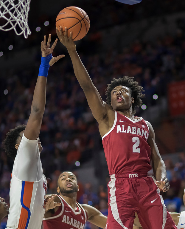 . Alabama guard Collin Sexton (2) drives to the basket over Florida forward Dontay Bassett (21) during the first half of an NCAA college basketball game in Gainesville, Fla., Saturday, Feb. 3, 2018. (AP Photo/Ron Irby)