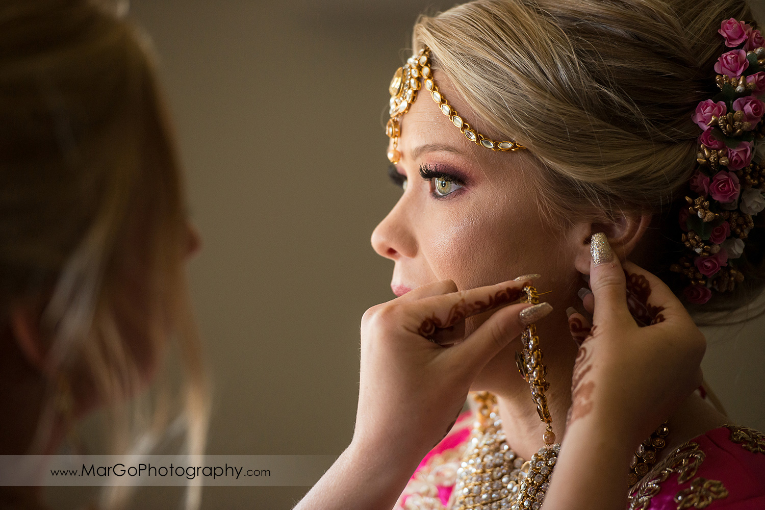 Indian bride getting ready - putting on golden earrings